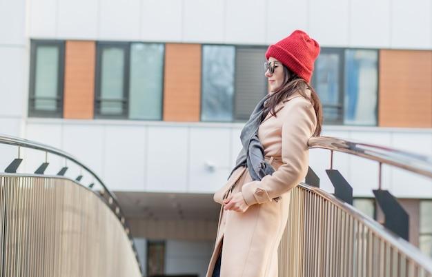 サングラス、赤い帽子、コートを着た女性が秋の街の橋の上に立っています。