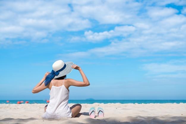 日没のビーチでリラックスした太陽の帽子の女性トロピカルと遠隔のビーチ