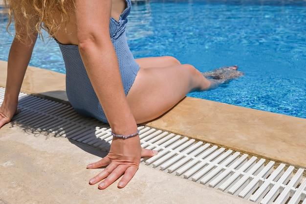 休日に日光浴をしているプールの近くのサングラスとビキニの女性。