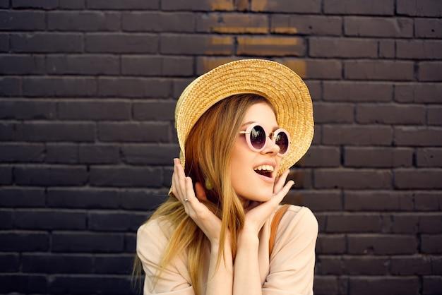 선글라스와 장식 모자에있는 여자는 백그라운드에서 야외 벽돌 벽을 산책.