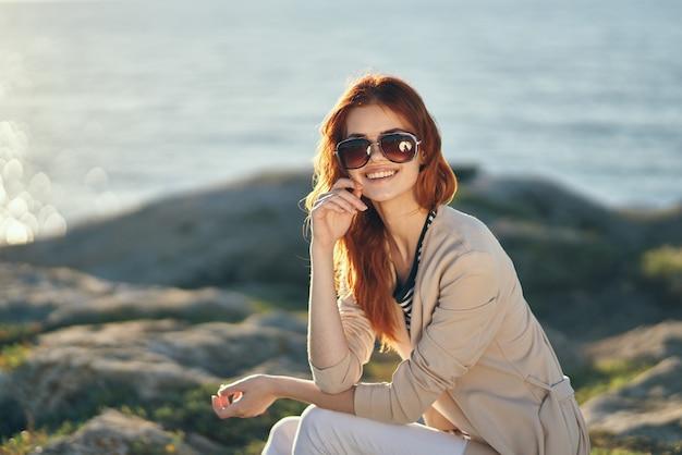 海の海のサングラスとピンクのセーターパンツの岩の女性