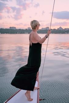Женщина в солнечных очках и длинном черном платье, наслаждаясь закатом на яхте в море