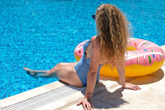 풍선 도넛 형 수영장 포즈 선글라스에 여자
