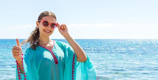 엄지 손가락을 보여주는 선글라스에 여자