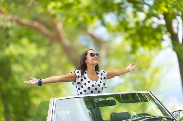 サングラスをかけた女性がコンバーチブルの上に座り、腕を大きく開いて、太陽と新鮮な空気を吸収します。