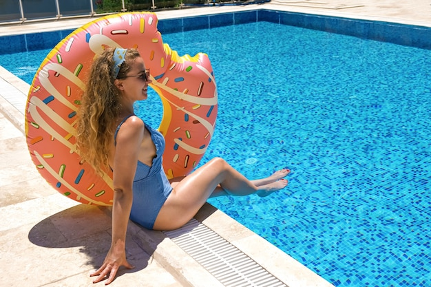 리조트 수영장 근처 풍선 도넛과 선글라스에 여자
