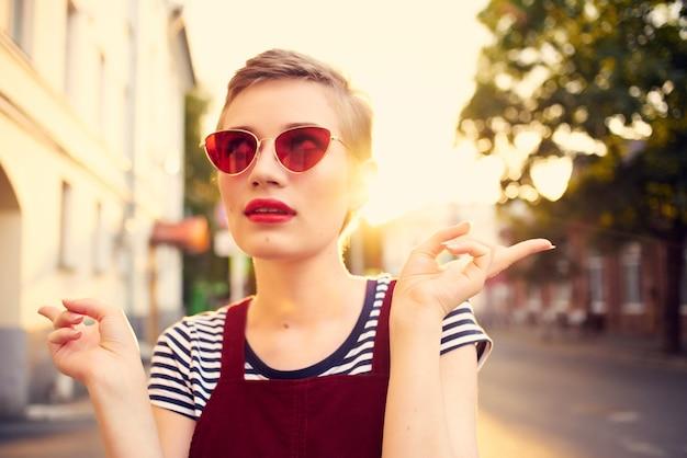 短い髪の屋外ロマンスポーズのサングラスの女性。高品質の写真