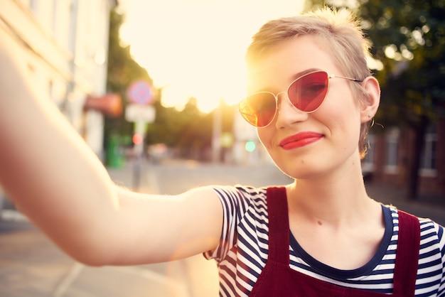 短い髪の屋外ロマンスポーズのサングラスの女性