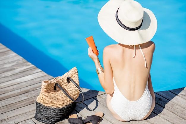 青い水と盆地の近くの日焼け止めローションと一緒に座っている日焼け止めの女性。日焼け止めソーラークリームuv保護コンセプト