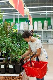 鉢植えの茂みを持つ部門の近くのスーパーマーケットの女性