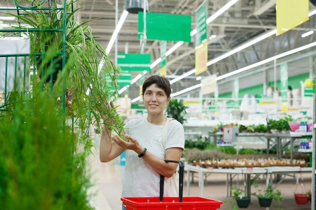 鉢植えの屋内花を持つ部門の近くのスーパーマーケットの女性