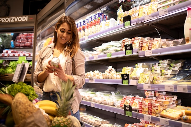 선반에 의해 제품에서 영양 값을 읽는 슈퍼마켓에서 여자
