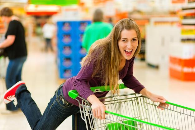ショッピングカートとスーパーマーケットの女性