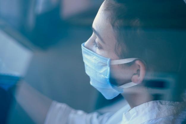 外科用フェイスマスクと手袋の車の運転の女性
