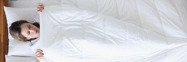 Женщина с удивлением смотрит под одеяло в постели, вид сверху, концепция тяжелой менструации