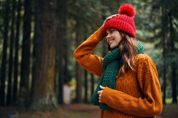 セーターと帽子をかぶった女性が秋のトリミングされたビューで森の中を自然の中を歩いています