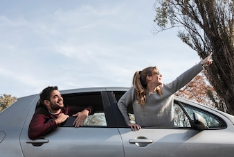 Woman in sweater hanging out of car window