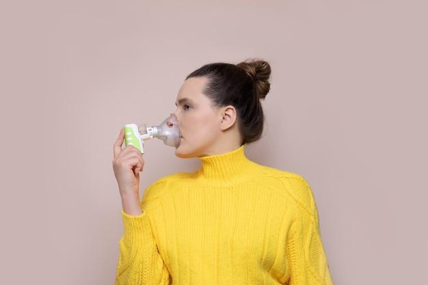 분홍색 배경에 스웨터에 여자는 무선 분무기로 호흡기를 흡입합니다.