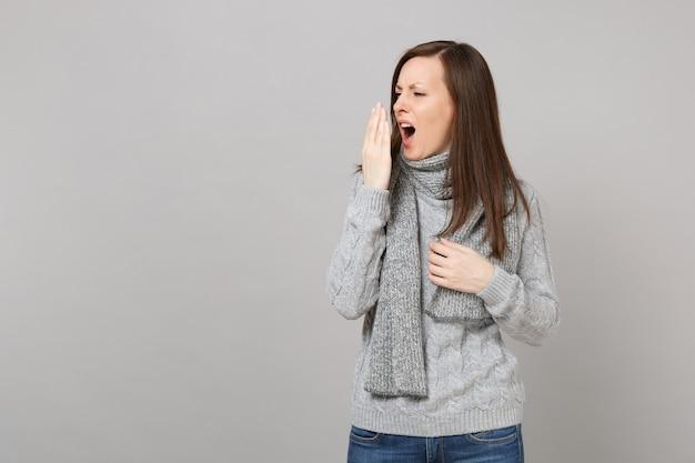 セーターを着た女性、脇を向いているスカーフ、くしゃみや咳、灰色の背景で隔離の手で口を覆っています。健康的なライフスタイルの病気の病気の治療、風邪の季節の概念。コピースペースをモックアップします。
