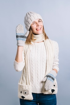 Woman in sweater showing greeting gesture