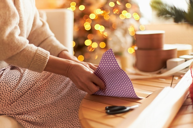 セーターを着て座ってギフト包装をしている女性