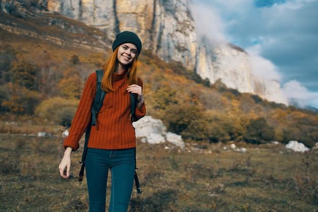 秋の旅行観光モデルで、セーターを着た女性が屋外でカメラに手を伸ばす