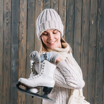 Woman in sweater with skates behind back