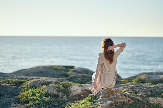 山の海の近くの石の上に手を上げてセーターを着た女性