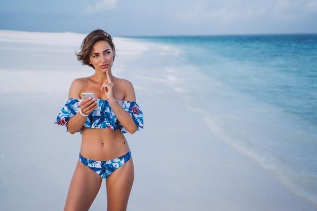 Женщина в купальных костюмах на берегу океана с помощью телефона