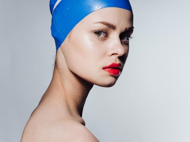 Женщина в шапочке для плавания с красными губами макияж модели обнаженные плечи. фото высокого качества