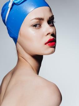 Женщина в шапочке для плавания с красными губами, модель макияжа, обнаженные плечи