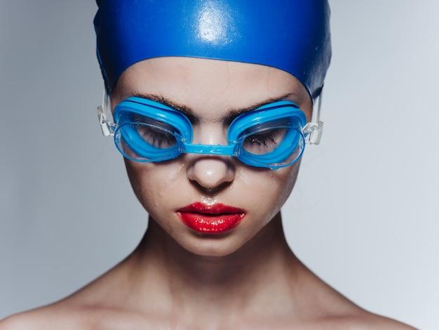 Женщина в плавательных очках и синей кепке с закрытыми глазами обрезанный вид