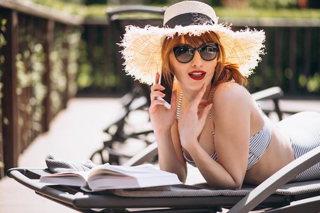 Женщина в купальнике лежит на кровати и читает книгу