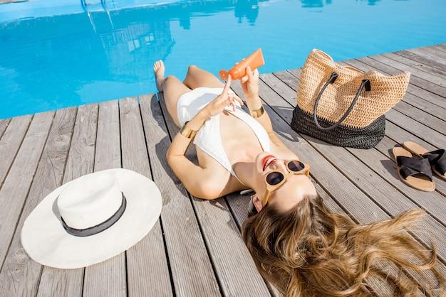 屋外の盆地の近くに横たわっている日焼け止めローションを適用する水着の女性。日焼け止めソーラークリームuv保護コンセプト