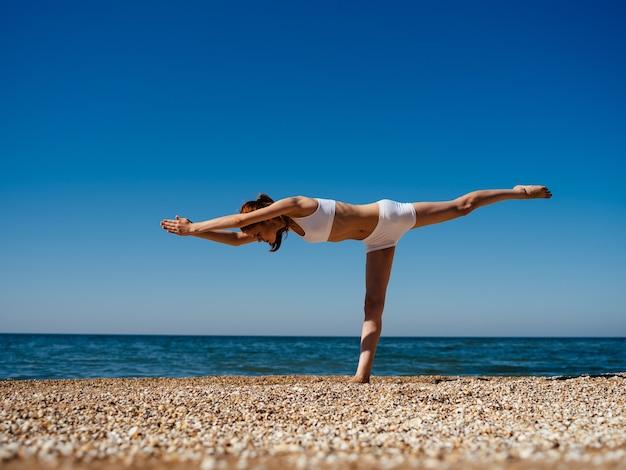 自然のビーチの風景で水着運動トレーニングの女性