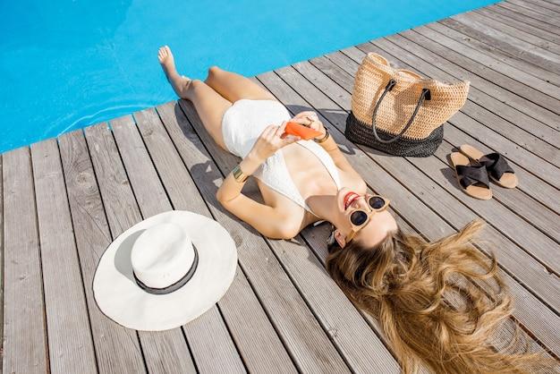 屋外の洗面器の近くに横たわっている日焼け止めローションとチューブを保持している水着の女性。日焼け止めソーラークリームuv保護コンセプト