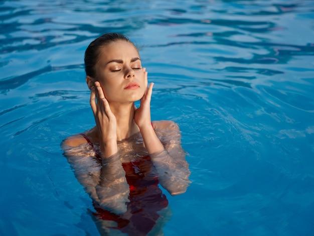 屋外のプールで水着姿の女性は目を閉じて贅沢なレジャー