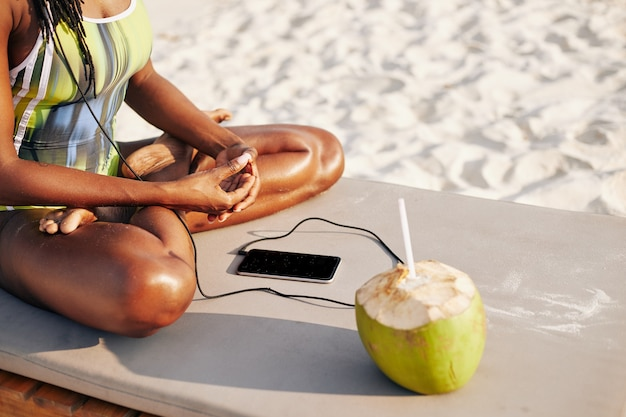 Женщина в купальнике, слушающая музыку