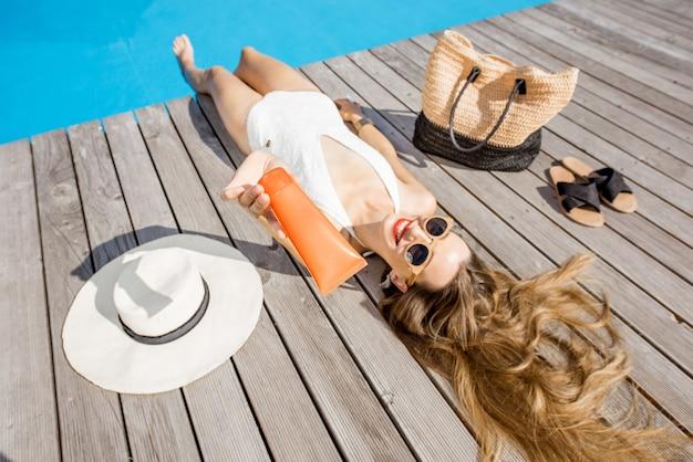 屋外の洗面器の近くに横たわっている日焼け止めローションのチューブを示す水着の女性。日焼け止めソーラークリームuv保護コンセプト
