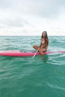 Женщина в купальнике занимается серфингом на гавайях