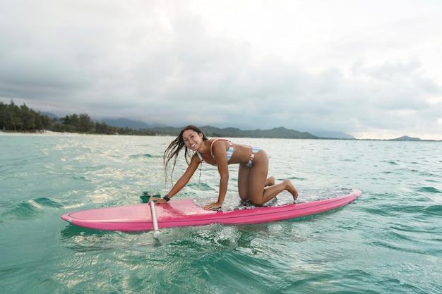 ハワイでサーフィンをしている水着の女性