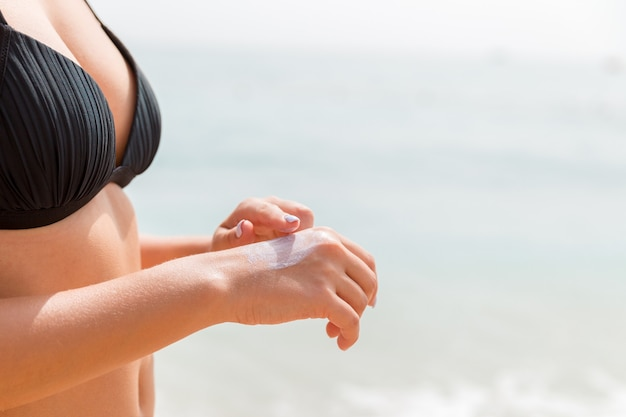 水着の女性は、海の背景に彼女の指で彼女の手に日焼け止めクリームを適用しています。