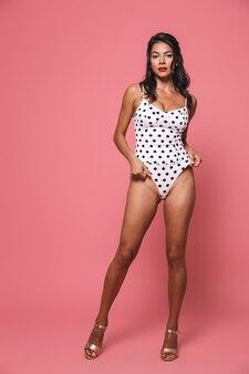 분홍색 벽에 고립 된 수영복 포즈에 여자입니다.