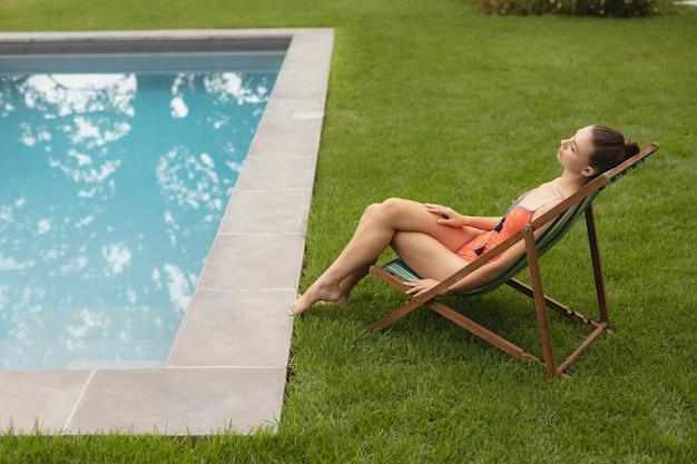 Женщина в купальных костюмах спит на шезлонге возле бассейна на заднем дворе