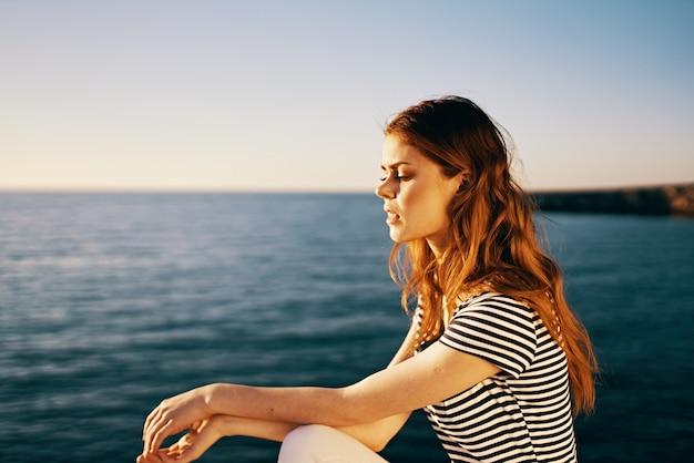 Tシャツと白いズボンの肖像画の海の夕日の女性