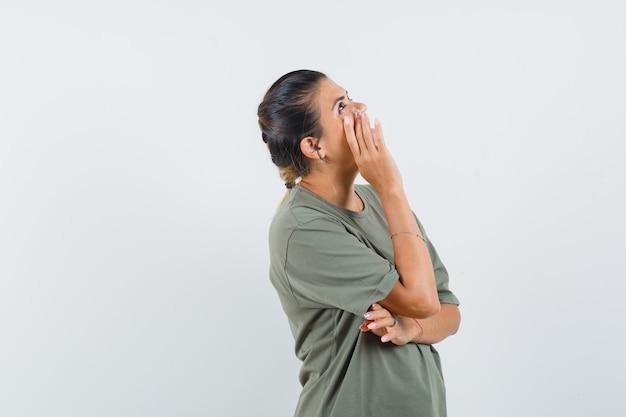 Женщина в футболке держит руку на щеке и выглядит мечтательно.