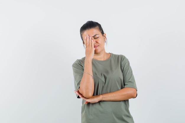 Женщина в футболке держит руку на лице и выглядит задумчивой