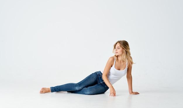 Tシャツの女性は床に横たわっているライフスタイルスタジオ孤立した背景