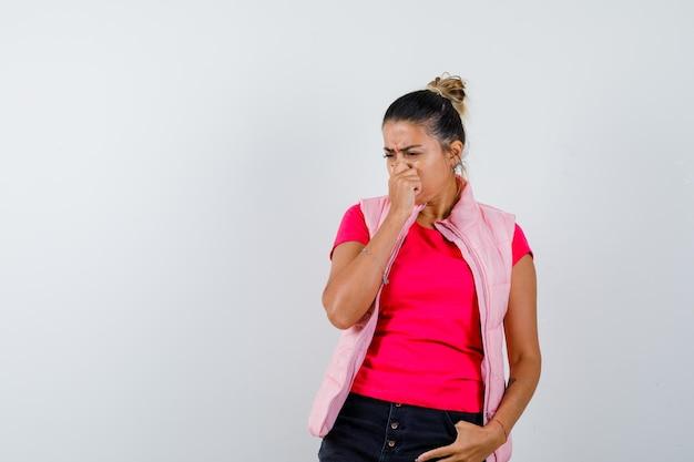 Женщина в футболке, жилетке зажимает нос, чувствует неприятный запах и выглядит с отвращением
