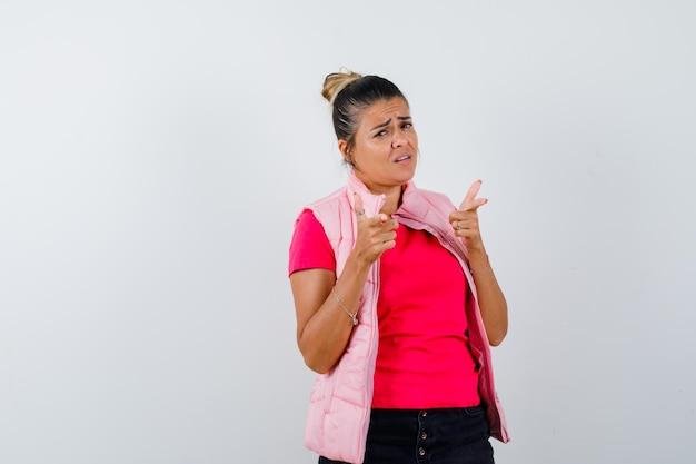 Женщина в футболке, жилете, указывающая на камеру и грустная